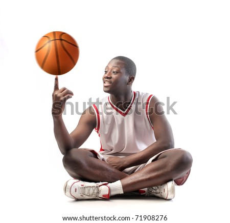 Smiling basketball player holding a basketball on his finger - stock photo
