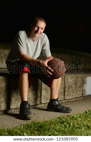 Smiling basketball player sitting down to rest, while looking at camera - stock photo
