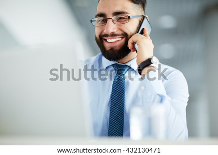Smiling bearded businessman talking on the phone at office - stock photo