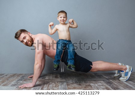 Smiling bearded father doing push-ups with little son sitting on his back over grey background - stock photo