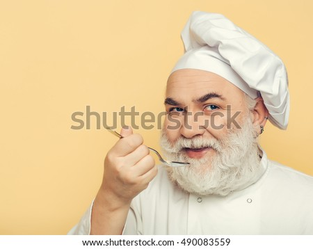 Smiling bearded man cook in hat tasting food with spoon in studio on yellow background
