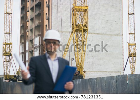 Smiling bearded young worker in helmet holding tool box