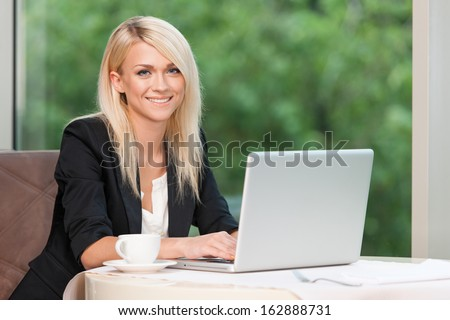 Smiling beautiful blond business woman with laptop. Drinking coffee at the restaurant