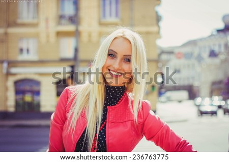 Smiling beautiful blond woman on the street in a red coat