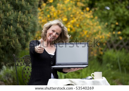 smiling beautiful blond woman presenting a laptop and posing thumbs up