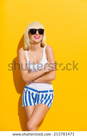 Smiling beautiful blonde young woman in a black sunglasses leaning on the wall with arms crossed. Three quarter length studio shot on yellow background. - stock photo