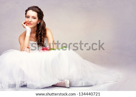 smiling beautiful brunette  bride sitting on the floor, vintage style photo