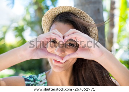 Smiling beautiful brunette doing heart shape with her hands and looking at camera - stock photo