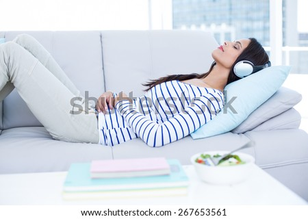Smiling beautiful brunette relaxing on the couch and listening music in the living room - stock photo