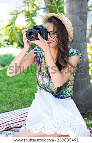 Smiling beautiful brunette sitting on the blanket and taking pictures with palm tree behind her - stock photo