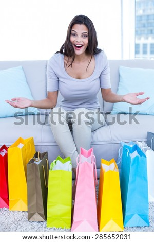 Smiling beautiful brunette sitting on the couch with shopping bags in the living room - stock photo