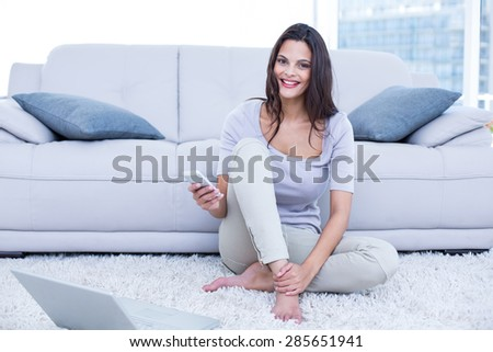Smiling beautiful brunette sitting on the floor and using her phone in the living room - stock photo