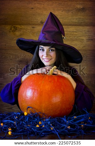 smiling beautiful brunette witch in ? purple hat and with a huge pumpkin