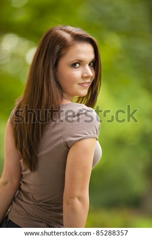 smiling beautiful brunette woman posing in a park