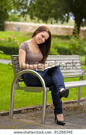 smiling beautiful brunette woman sitting on a bench in a park and reading a book