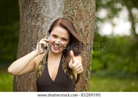 smiling beautiful brunette woman with a cell phone standing in a park next to a tree and posing with the thumbs up sign