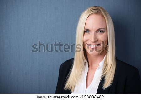 Smiling beautiful business woman with long blonde hair looking at the camera in front of a blue chalkboard background with copypsace - stock photo