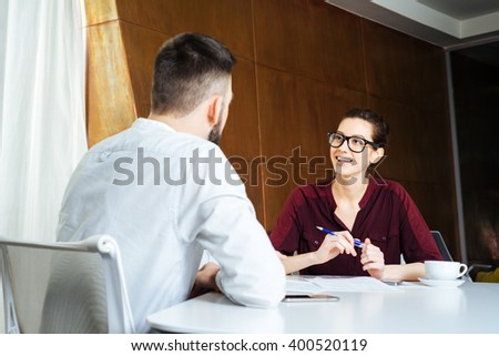 Smiling beautiful businesswoman in glasses talking to young businessman in meeting room - stock photo
