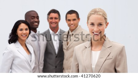 Smiling beautiful businesswoman leading her team against white background - stock photo