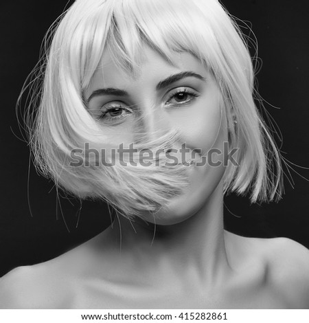 Smiling beautiful caucasian woman wearing colorful short hair wig isolated on black background. Black and white studio portrait