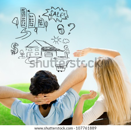 Smiling beautiful couple sitting on a bench at summer park and planning their future purchases - stock photo