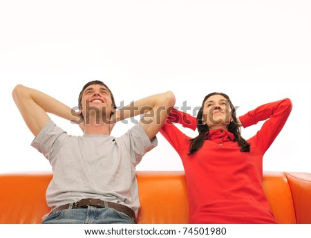 Smiling beautiful couple sitting on a sofa and dreaming about new home - stock photo