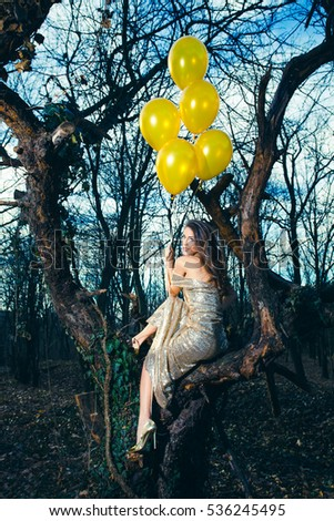 smiling beautiful  fashion woman wearing long elegant dress with balloons  in forest