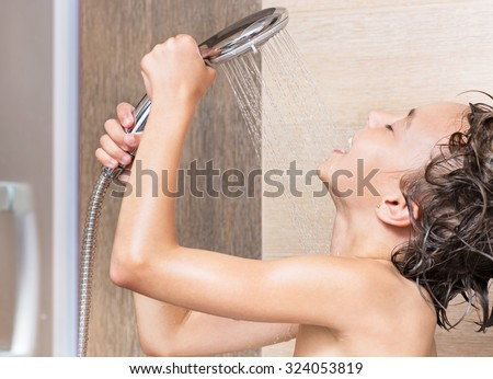 Smiling beautiful girl bathing under a shower at home - stock photo