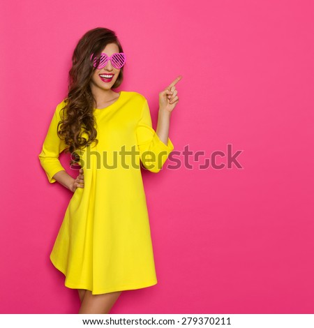 Smiling beautiful girl in pink sunglasses and yellow mini dress posing against pink background and pointing. Three quarter length studio shot. - stock photo