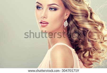 Smiling Beautiful girl light brown hair with an elegant hairstyle , hair wave ,curly - stock photo