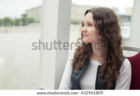 smiling beautiful girl looking out the window