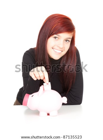 smiling beautiful girl putting five euro in piggy bank - stock photo