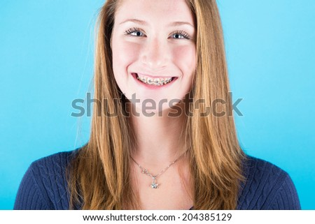 Smiling Beautiful Girl with Braces on Blue Background - stock photo