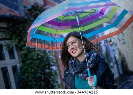 Smiling beautiful girl with her umbrella on a rainy day - stock photo
