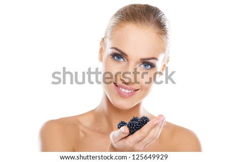 Smiling beautiful healthy woman with a lovely smile holding a handful of fresh blackberries - stock photo