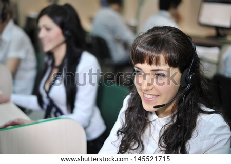 Smiling beautiful lady working at real call center with colleagues in office - stock photo
