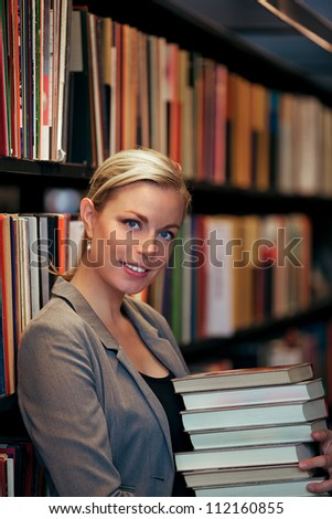 Smiling beautiful librarian or student carring a pile of books in a library as she either replaces them on the shelves or removes them for further research with copyspace - stock photo