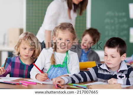 Smiling beautiful little girl in school with her friends sitting at a desk in the front of the classroom with a young boy and girl writing on a notebook - stock photo