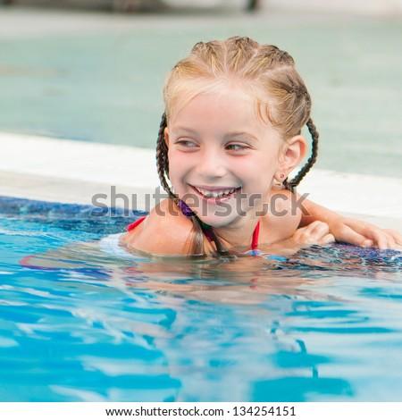 Smiling beautiful little girl in swimming pool - stock photo