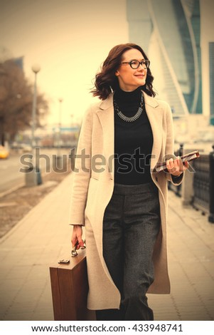 smiling beautiful middle-aged woman in a bright coat with a book and case goes forward. instagram image filter retro style