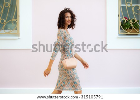 smiling beautiful middle-aged woman in a summer dress with handbag, walking along the light walls of the house - stock photo
