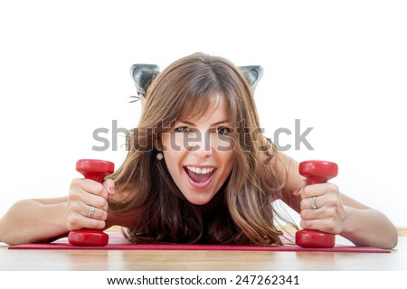 Smiling beautiful sporty fit athletic girl with weights or dumbbells wearing sports clothing lying on mat at gym exercise or working out. Weight loss young woman. Caucasian happy female fitness model - stock photo