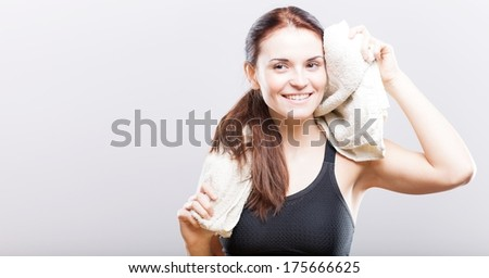 Smiling beautiful woman after training wiping face with towel