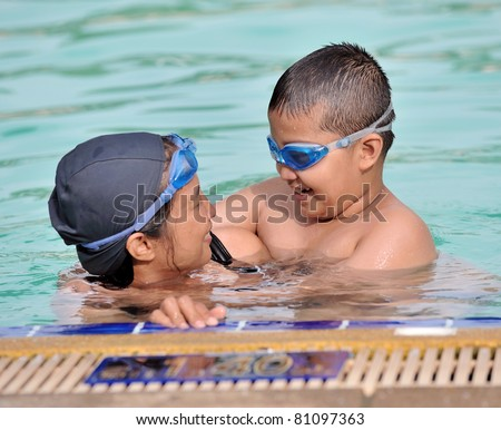 Smiling beautiful woman and boy in pool - stock photo