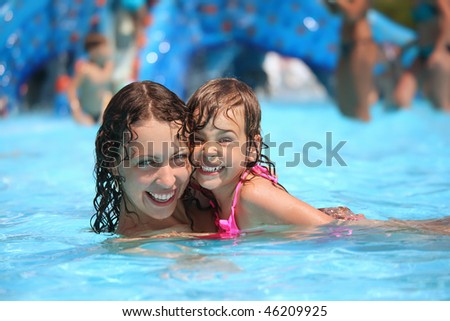 Smiling beautiful woman and little girl bathes in pool in aquapark - stock photo