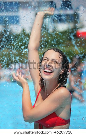 Smiling beautiful woman bathes in pool under water splashes, lifted hand upwards