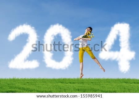 Smiling beautiful woman dancing with 2014 New Year clouds on the meadow
