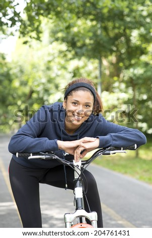 Smiling beautiful woman exercising with bicycle, outdoor.