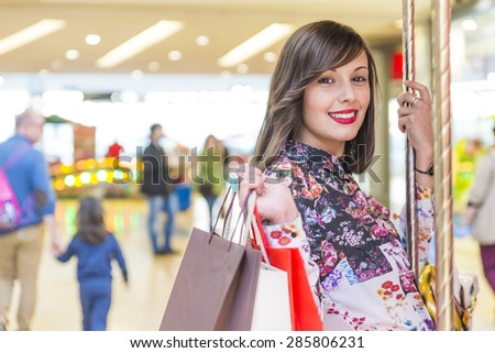 Smiling beautiful woman holding shopping bags on carousel - stock photo