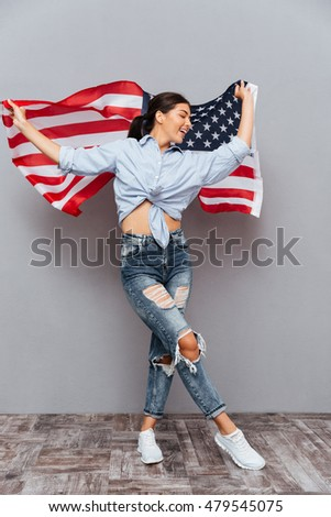 Smiling beautiful woman holding USA flag isolated on a gray background